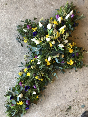 Seasonal British Funeral flower cross filled with spring flowers in York and Hull